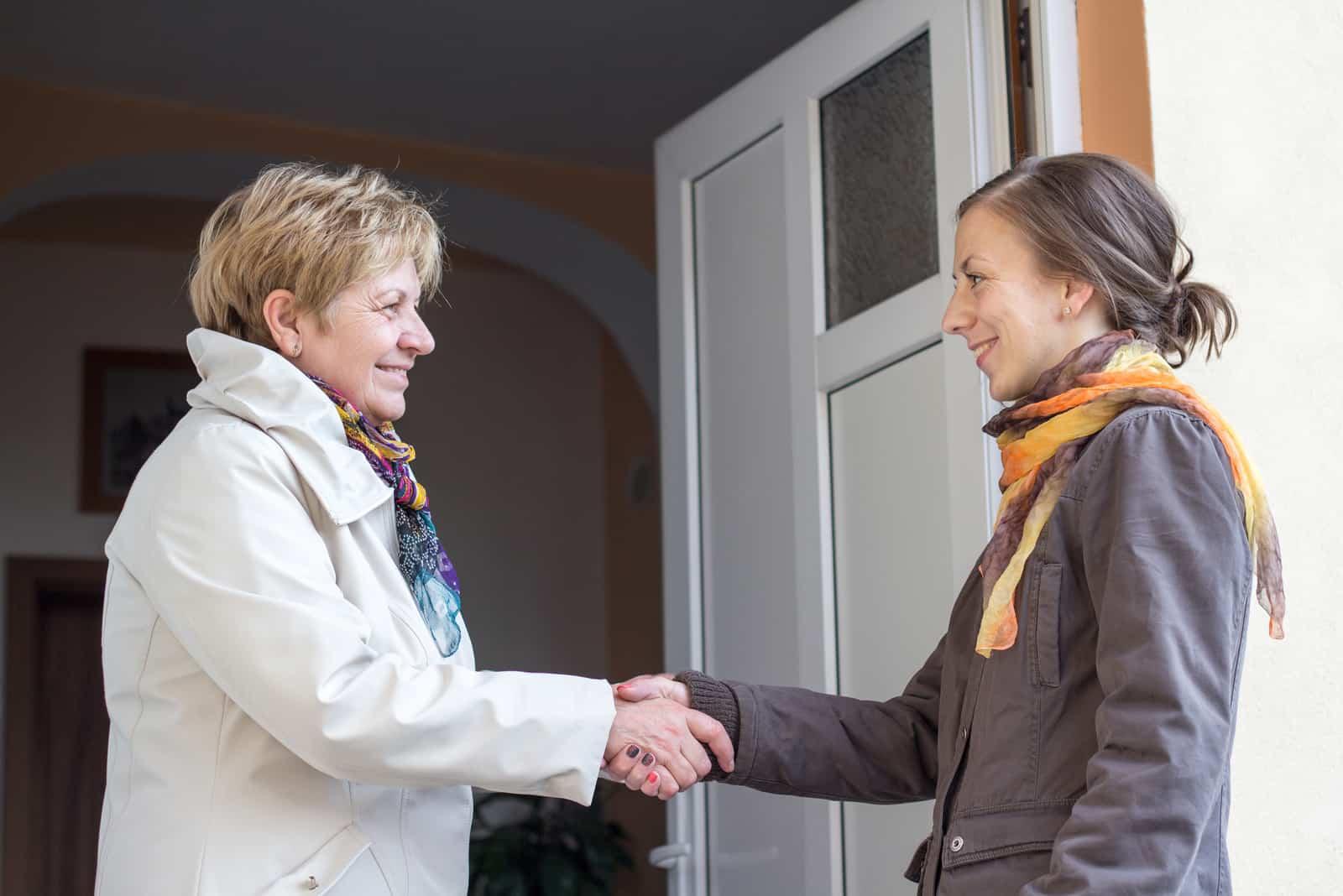 une femme souriante accueille ses voisins