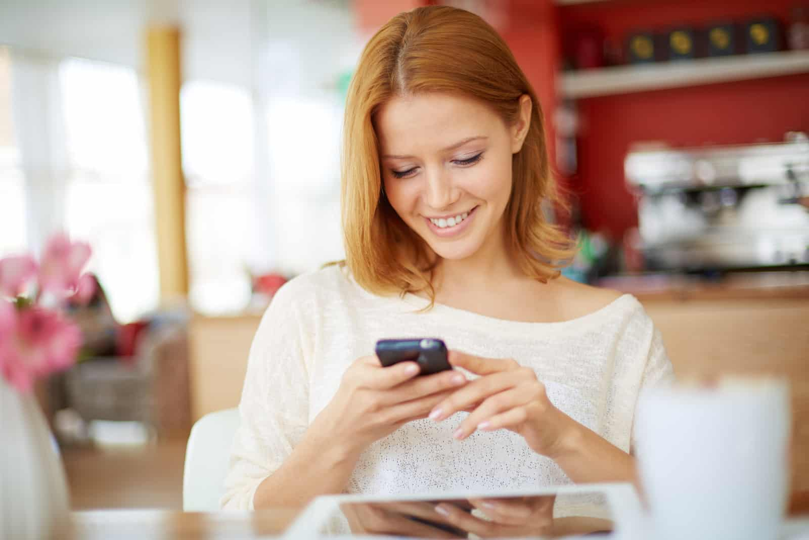 une femme souriante est assise et tient un téléphone dans sa main