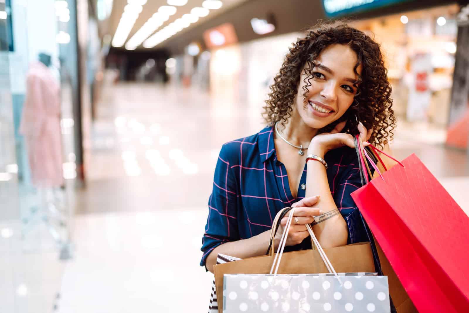une femme souriante parle au téléphone et tient des sacs à la main