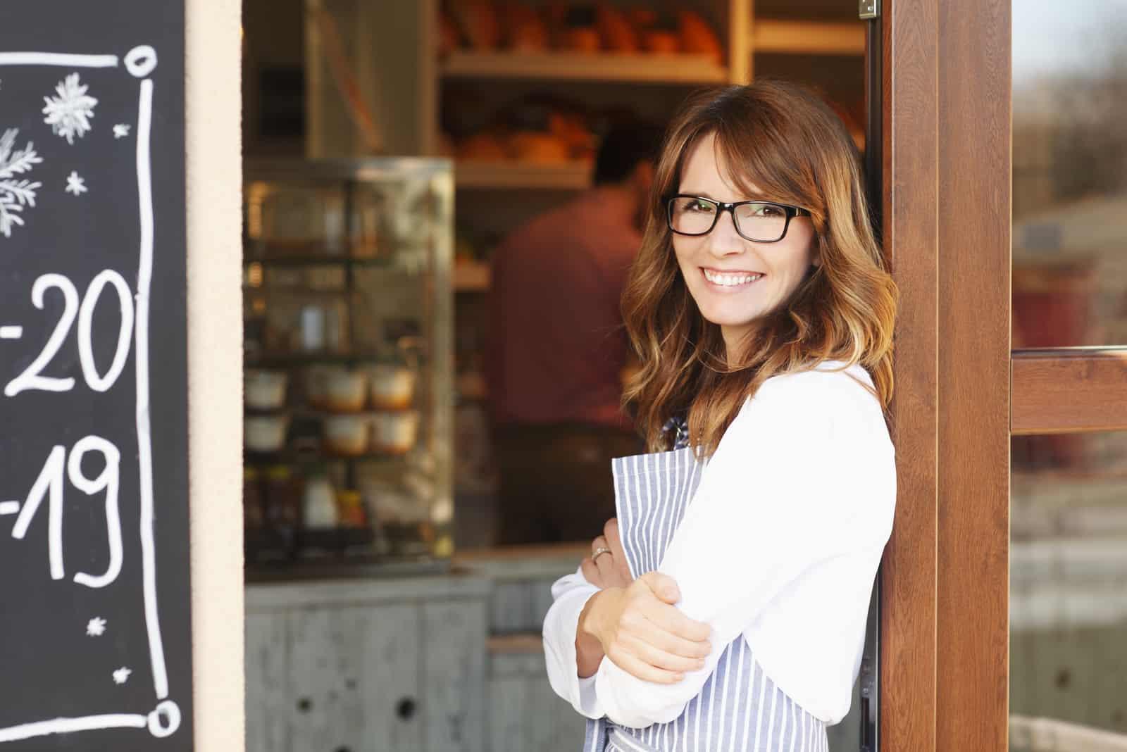 une femme souriante se tient à côté d'un café