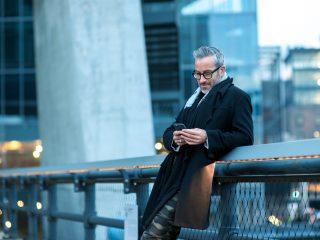 un homme se tient près de la clôture et écrit au téléphone