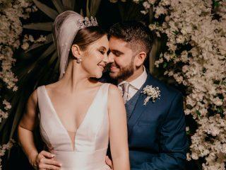 le marié et la mariée s'embrassant près de fleurs blanches