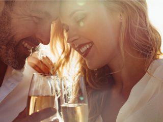 un homme souriant et une femme buvant du vin