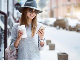 une femme souriante avec un chapeau sur la tête se lève et tient le téléphone dans sa main