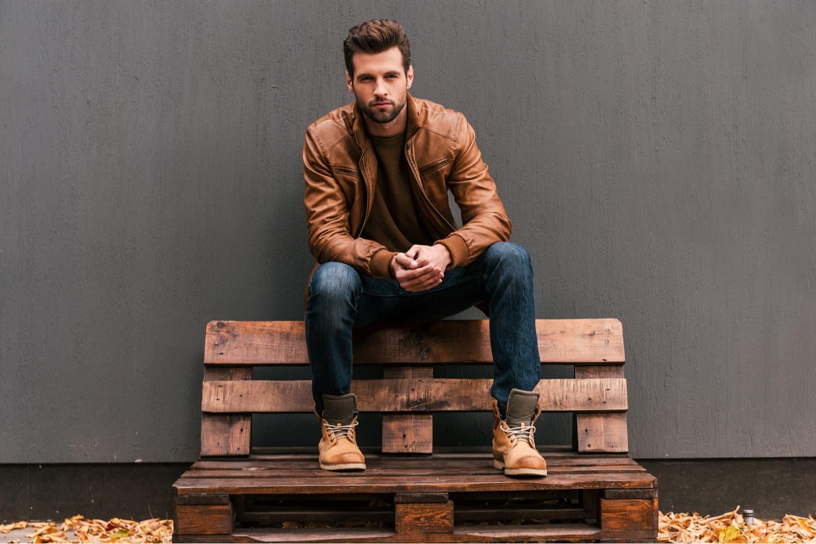 Beau jeune homme assis sur la palette en bois