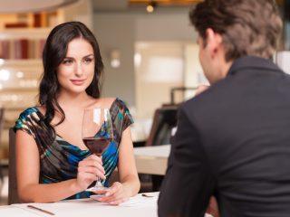 femme regardant un homme en tenant un verre de vin