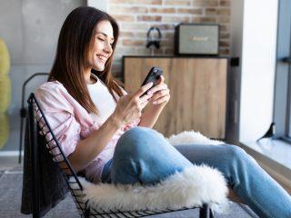 femme heureuse regardant son téléphone tout en étant assise sur une chaise