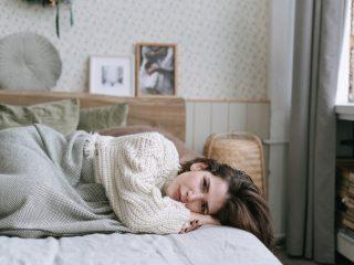 femme triste en chandail blanc allongée sur un lit
