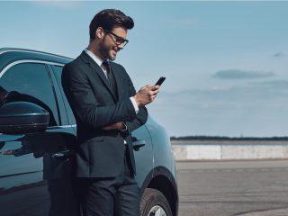 un homme se tient appuyé contre une voiture et un bouton du téléphone