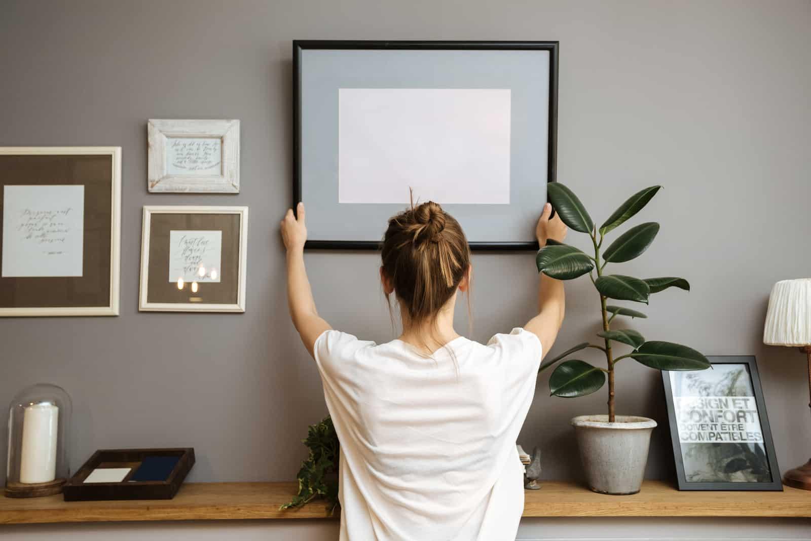 Fille accrochant un cadre sur un mur gris