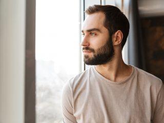 Jeune homme barbu sérieux debout à la fenêtre
