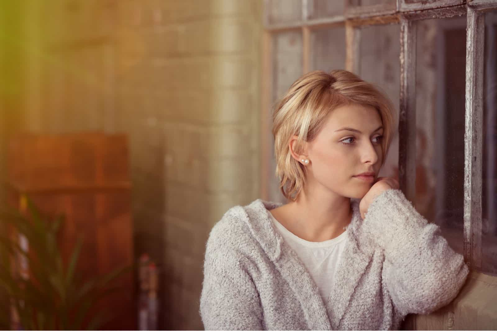 Jeune femme assise à rêvasser