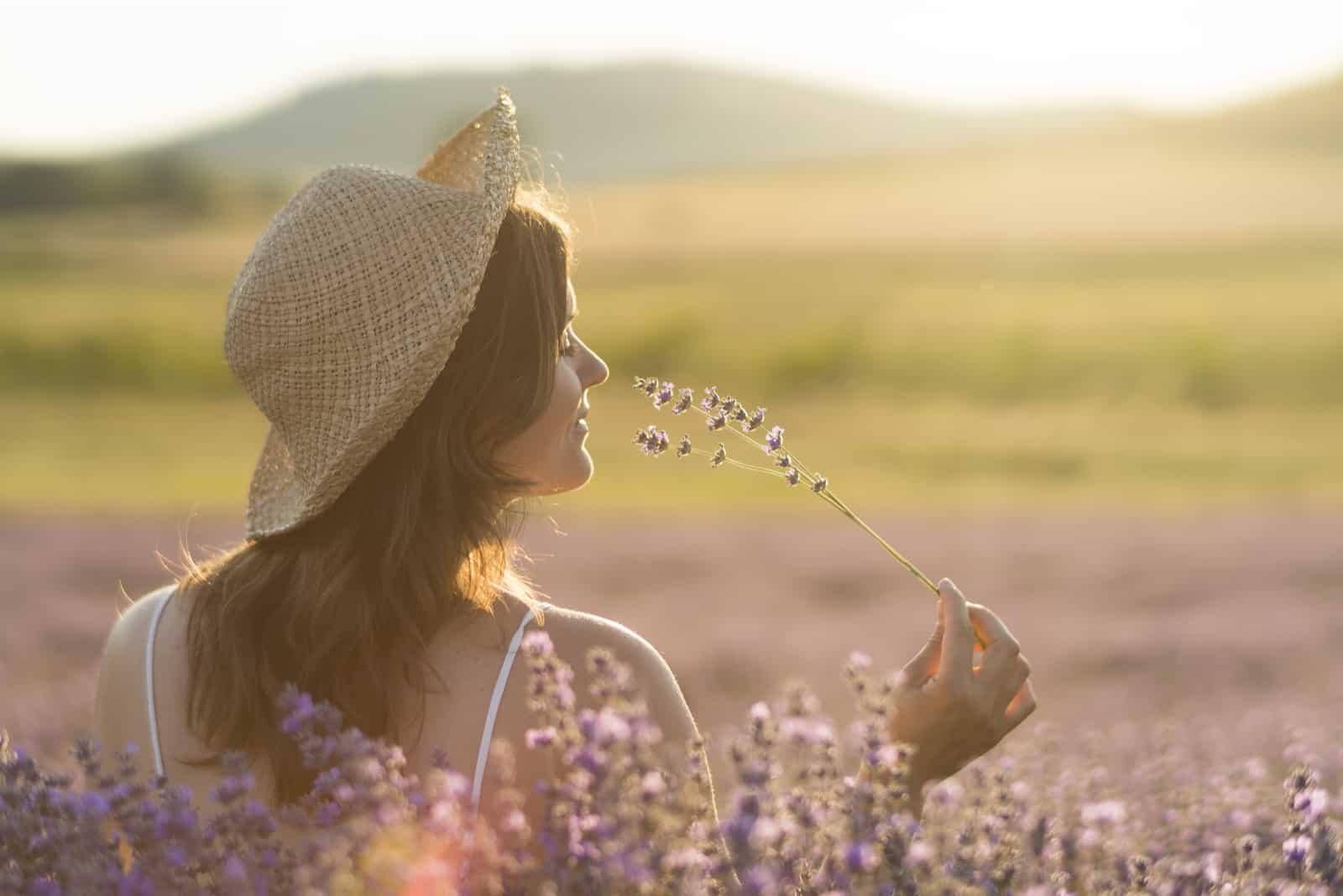 Jeune femme avec un chapeau de paille tenant un bouquet de fleurs de lavande