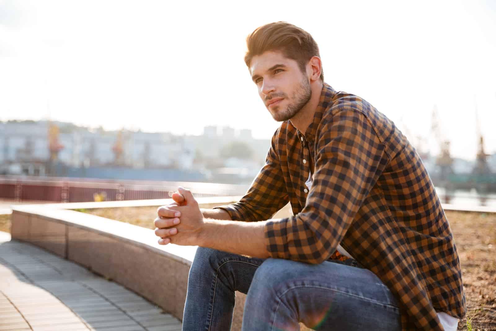 Jeune homme pensif en chemise à carreaux assis et pensant à l'extérieur