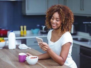 une femme souriante assise dans la cuisine et appuyant sur un téléphone