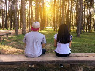 homme et femme assis sur un banc dans une forêt