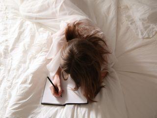 femme écrivant sur un cahier dans un lit