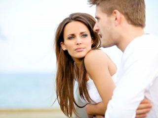 femme en haut blanc écoutant un homme