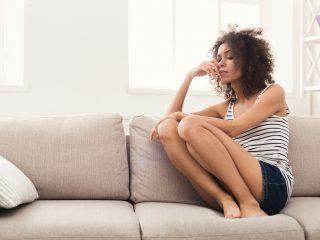 femme triste aux cheveux bouclés assise sur un canapé