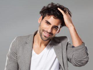 un homme souriant touche ses cheveux