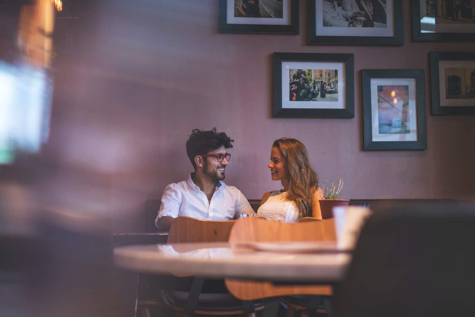 homme et femme établissant un contact visuel tout en étant assis à une table
