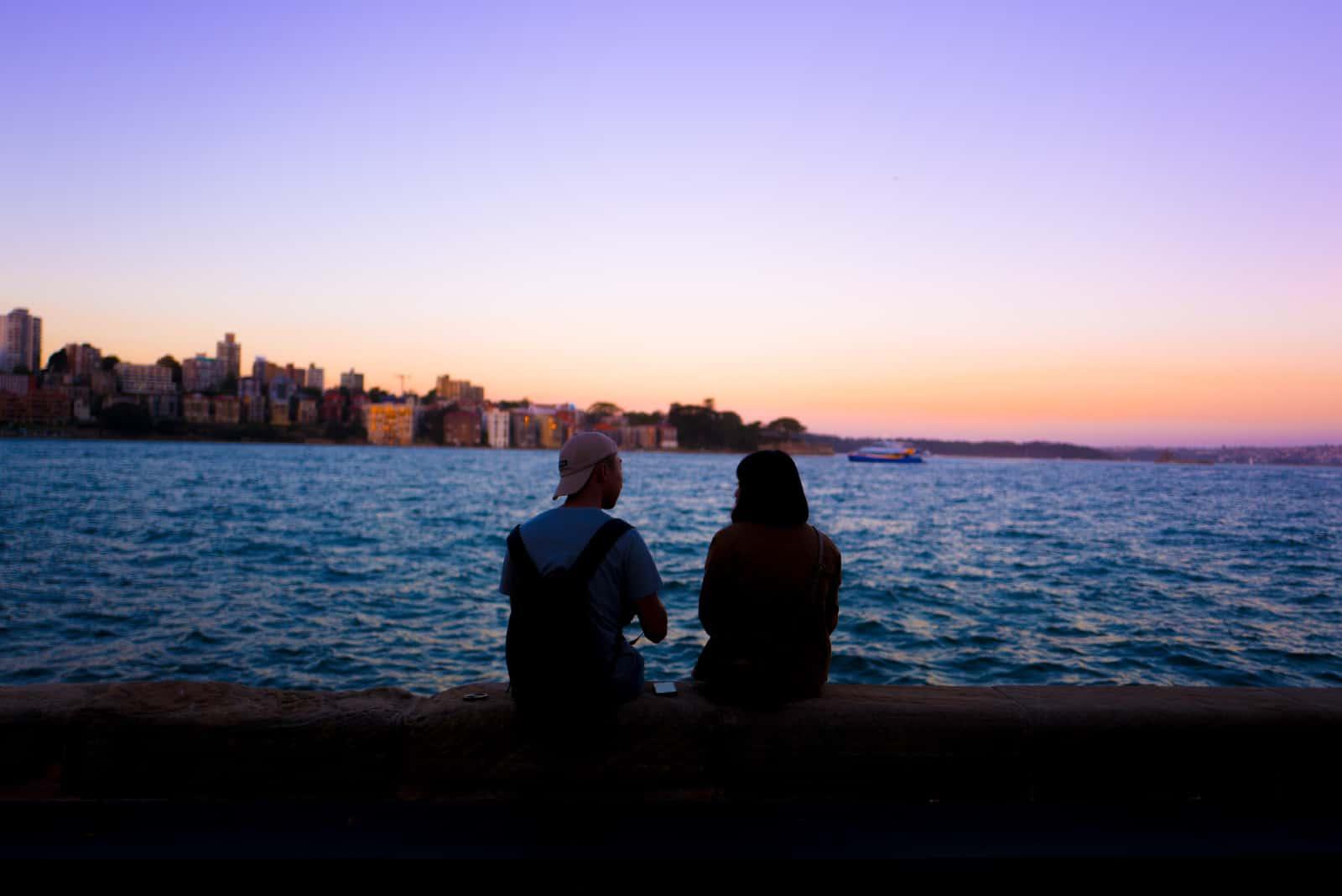 homme et femme parlant assis près de la mer