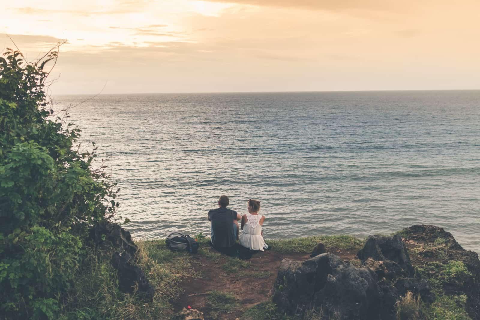 homme et femme en robe blanche assis près de la mer