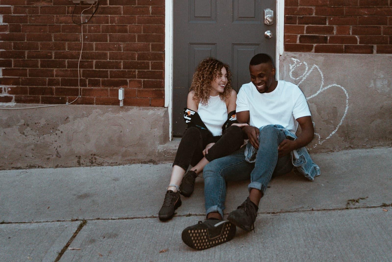homme en chemise blanche et femme assise près de la porte