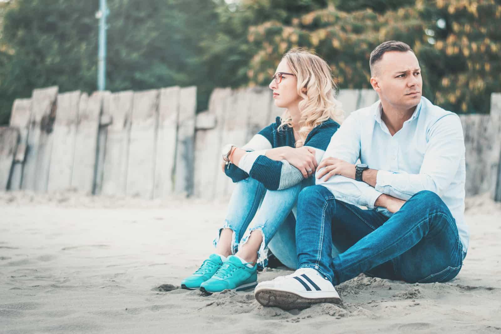 homme et femme tristes assis sur le sable près d'une clôture en bois