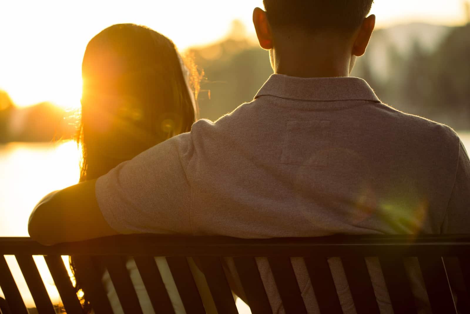 homme et femme assis sur un banc regardant l'eau