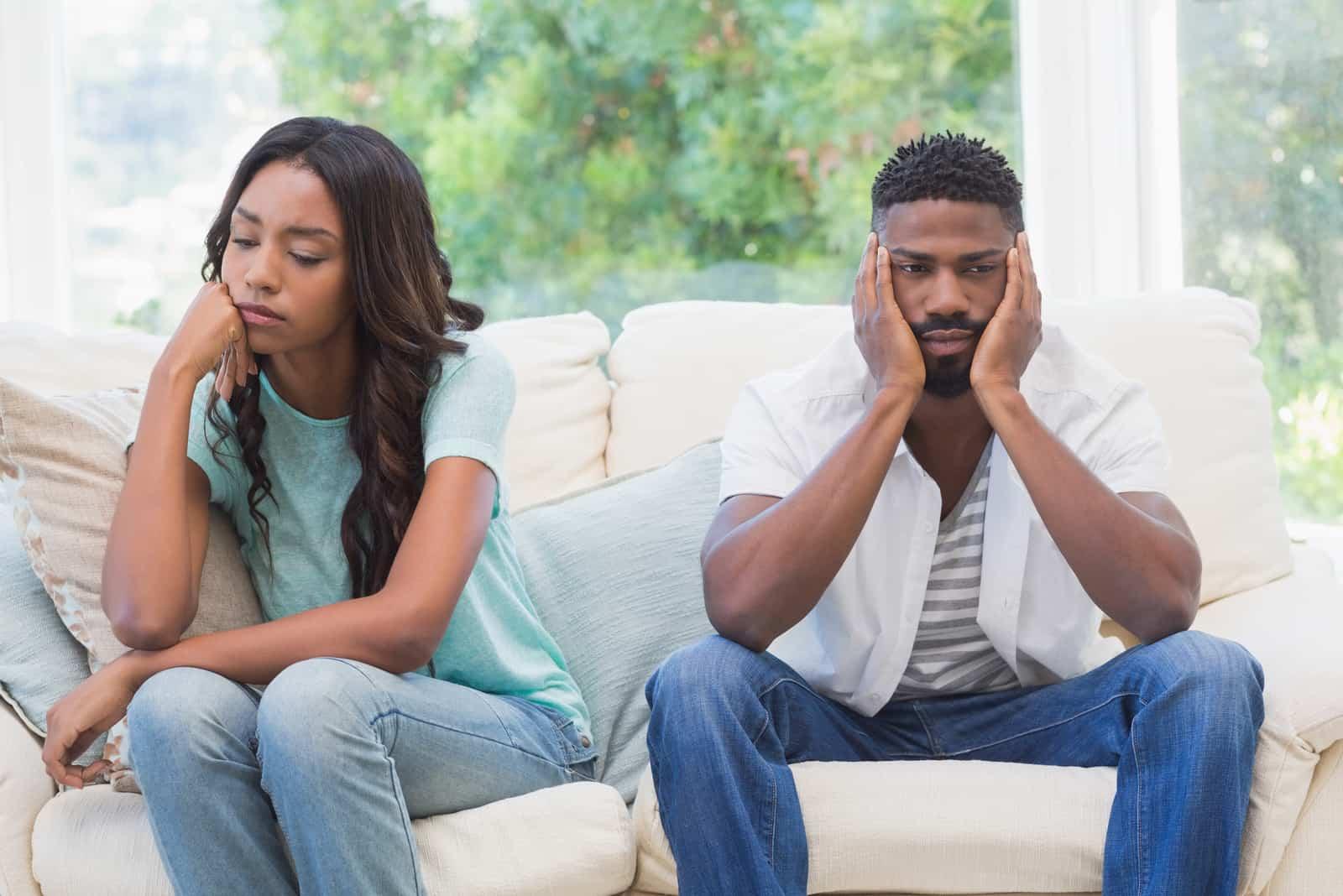 femme triste aux cheveux bouclés et homme assis sur un canapé