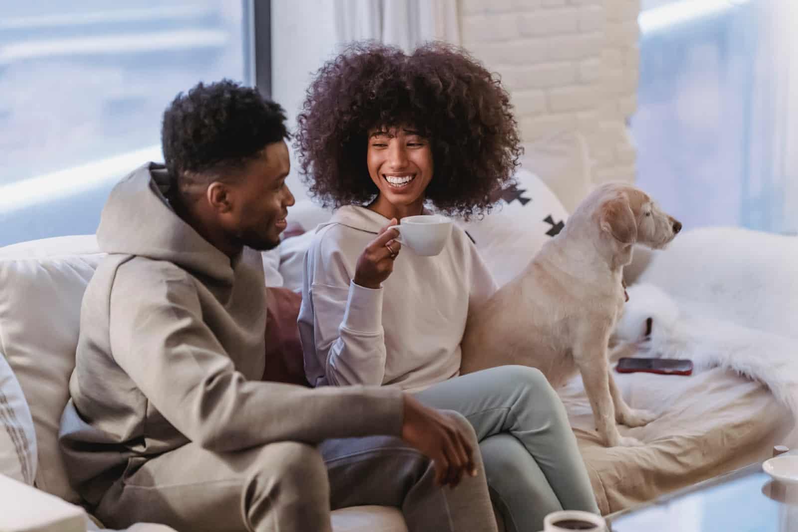 homme et femme souriant assis sur un canapé