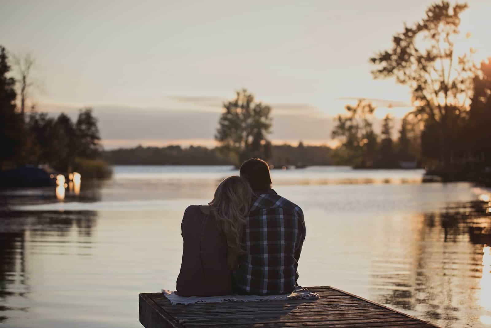 homme et femme assis sur un quai pendant le coucher du soleil