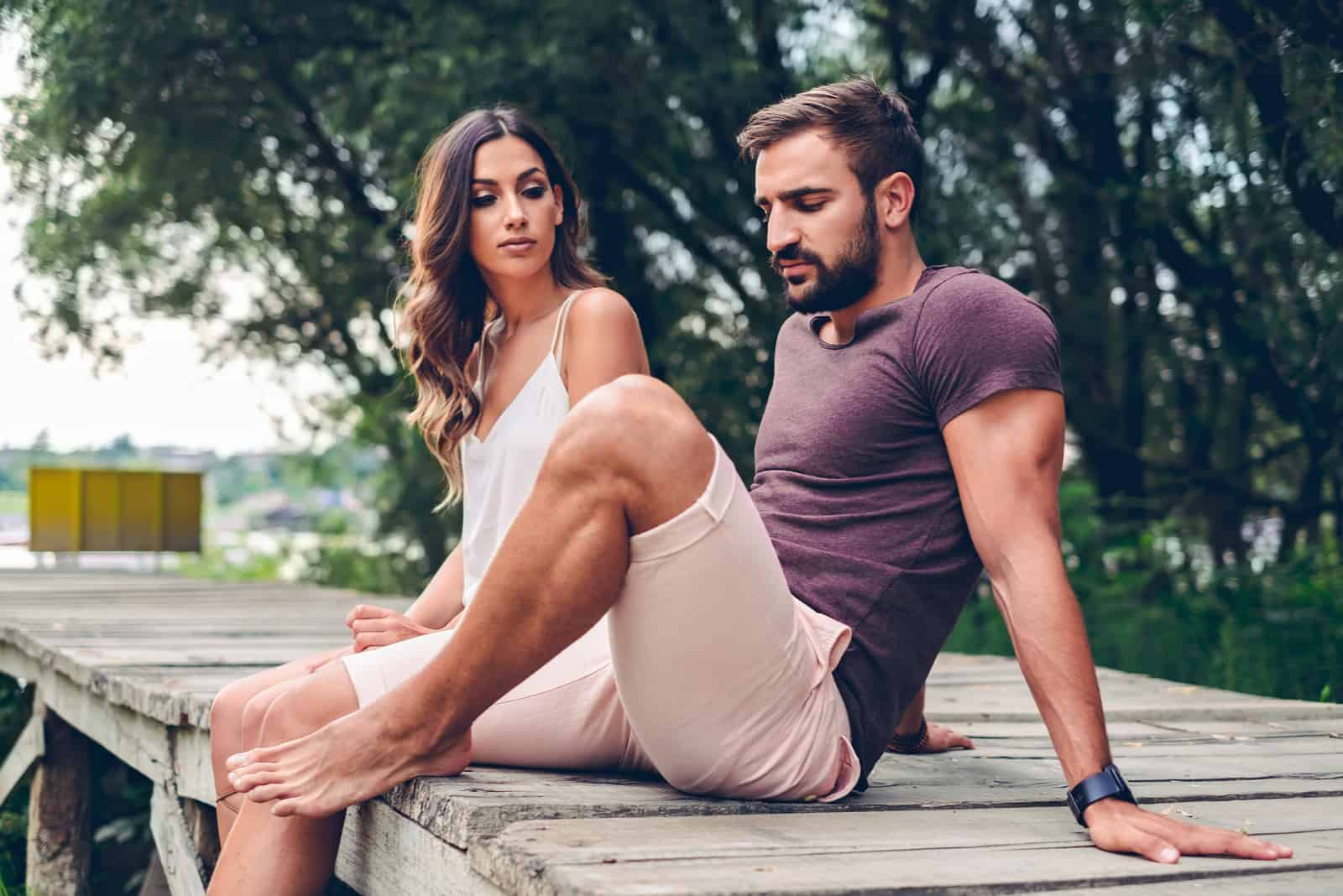 homme sa et femme en robe blanche assis sur un quai
