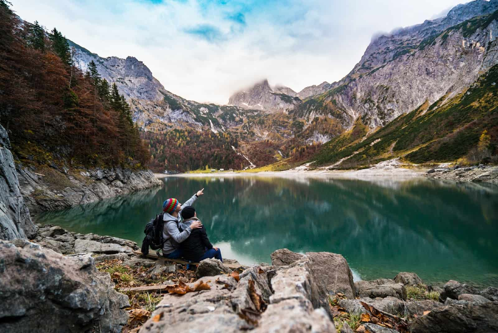 homme et femme assis sur un rocher près de l'eau