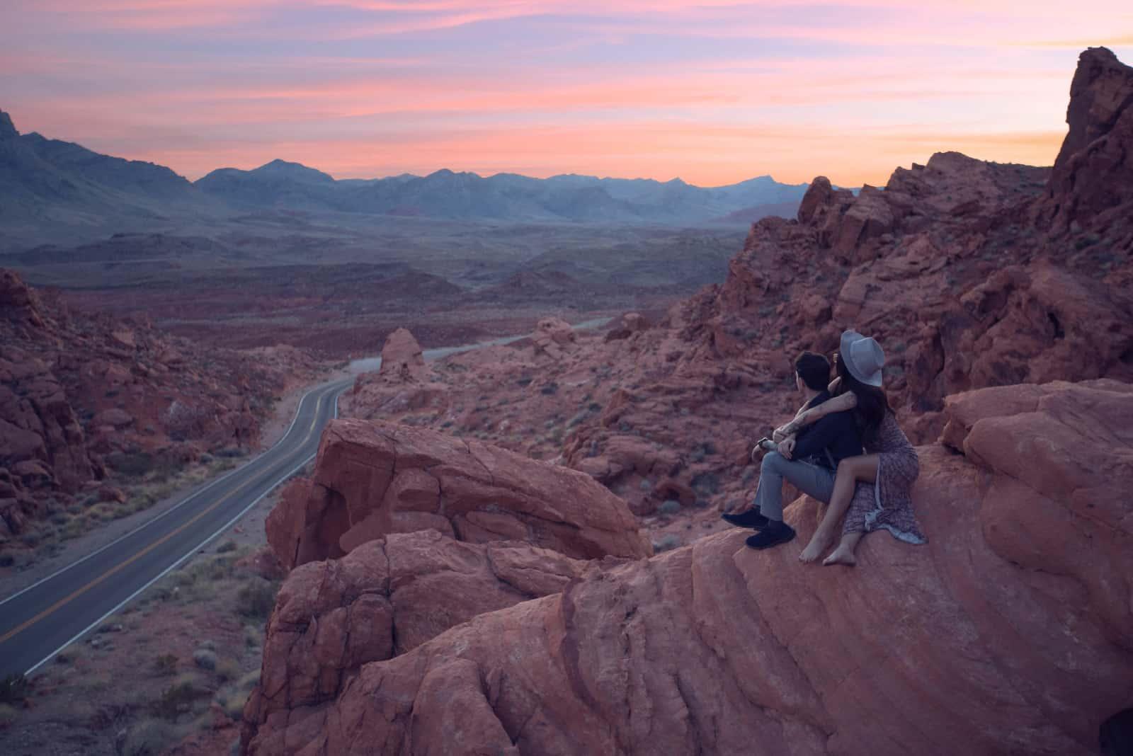 homme et femme assis sur un rocher pendant le coucher du soleil