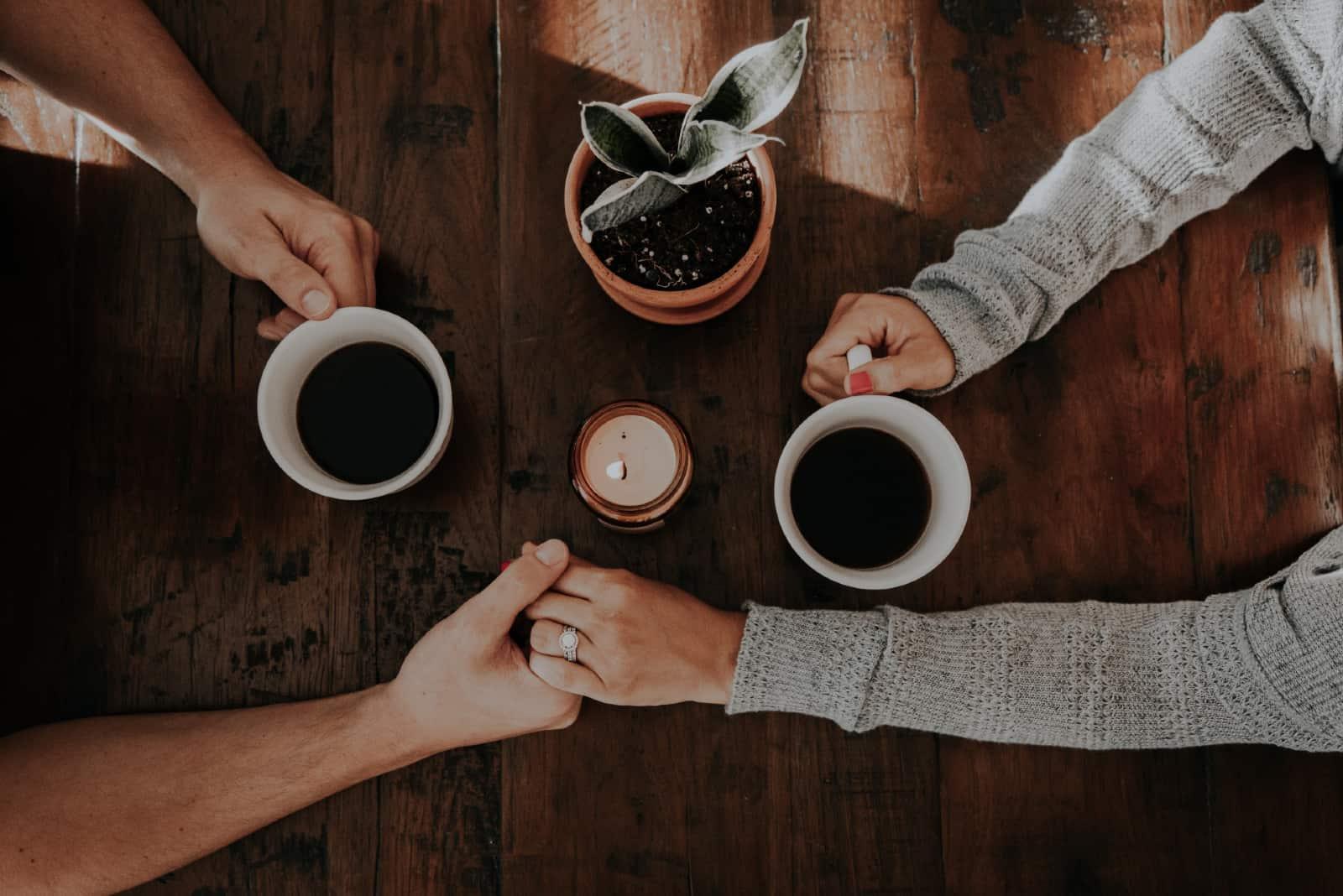 homme et femme se tenant la main en buvant du café