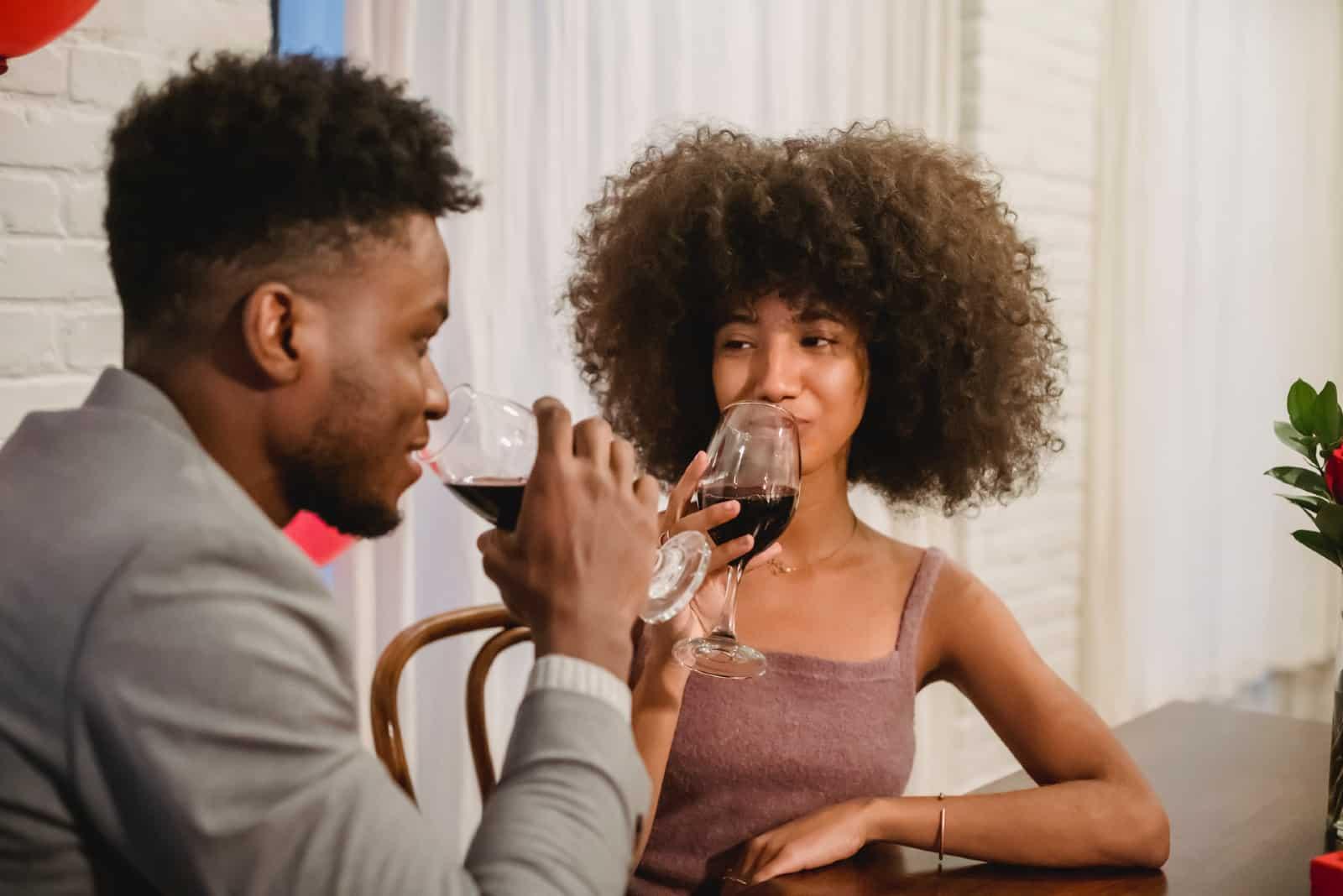 homme et femme buvant du vin assis à une table