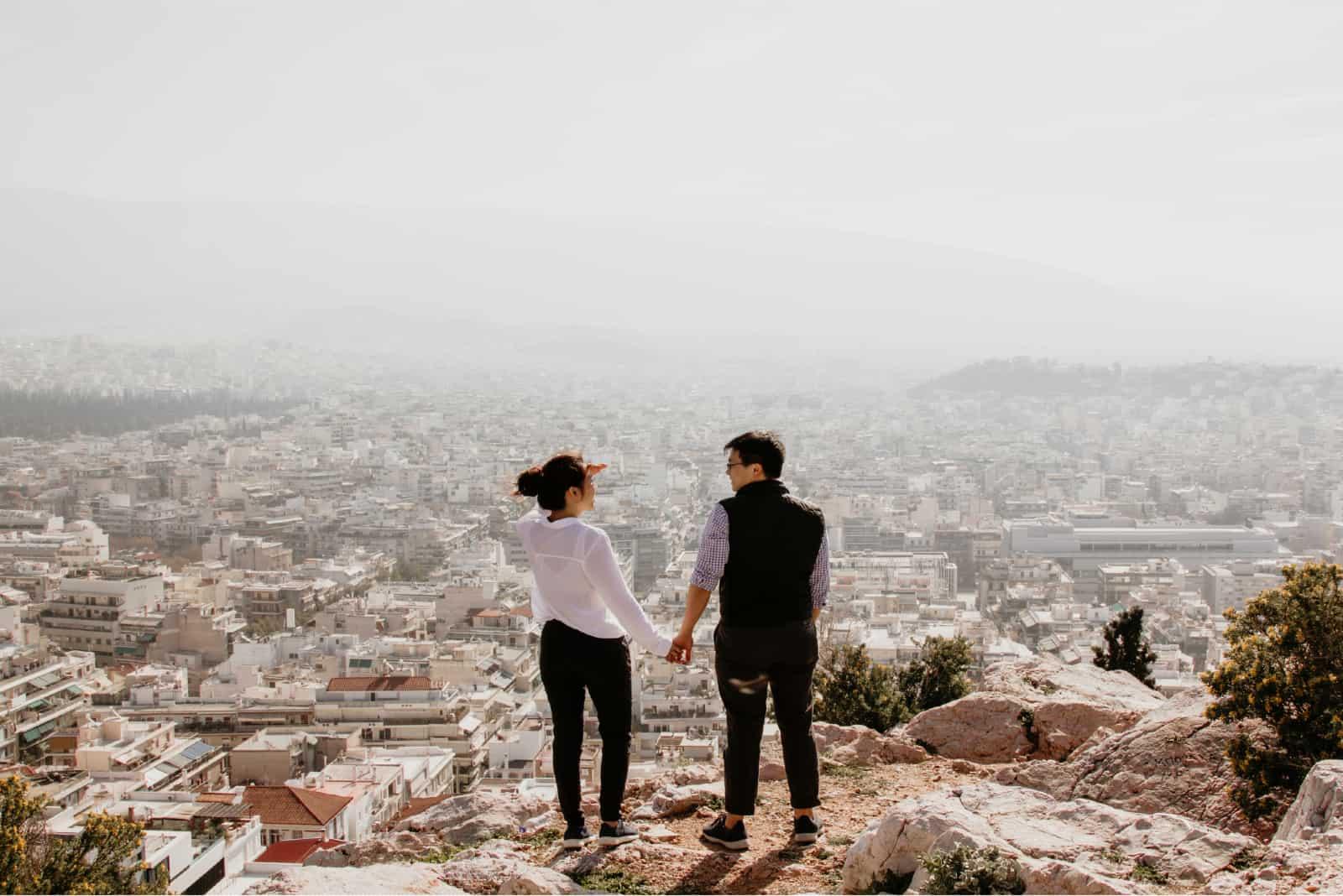 homme et femme se tenant la main en haut d'une falaise
