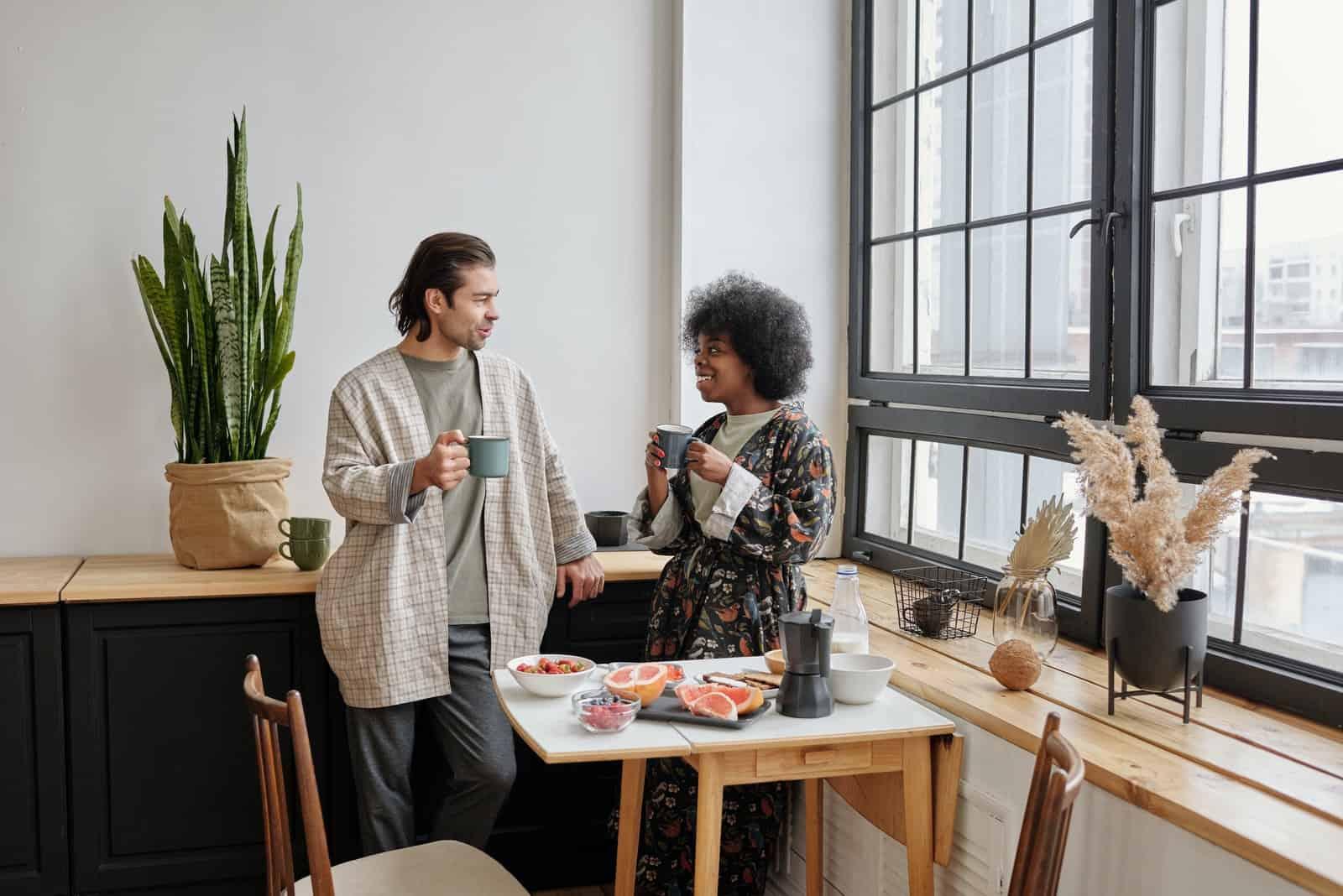 homme et femme buvant du café debout dans une cuisine
