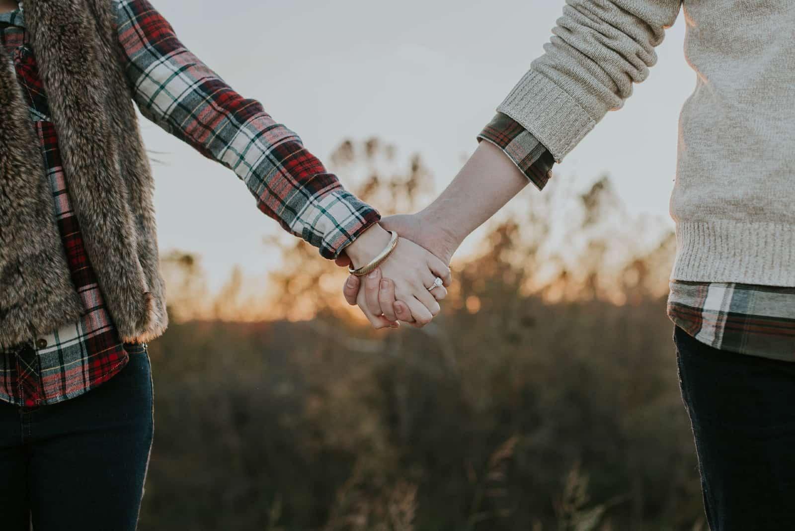 homme et femme se tenant la main dans un champ