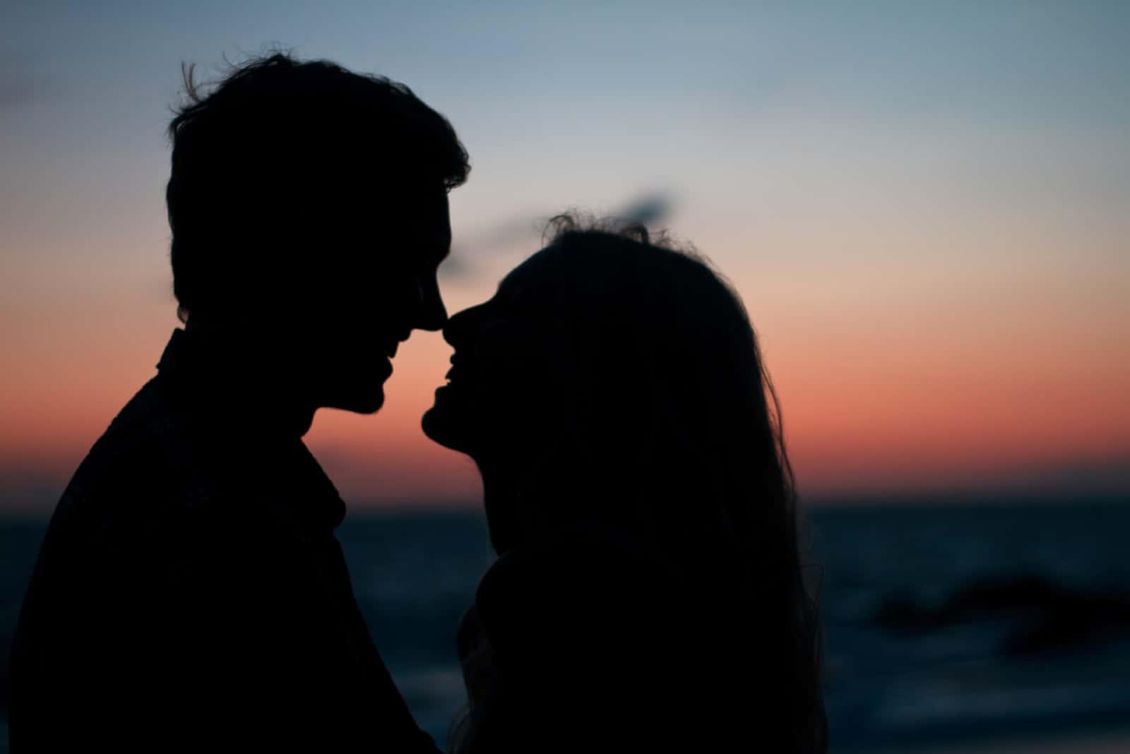homme et femme debout près de la mer pendant le coucher du soleil