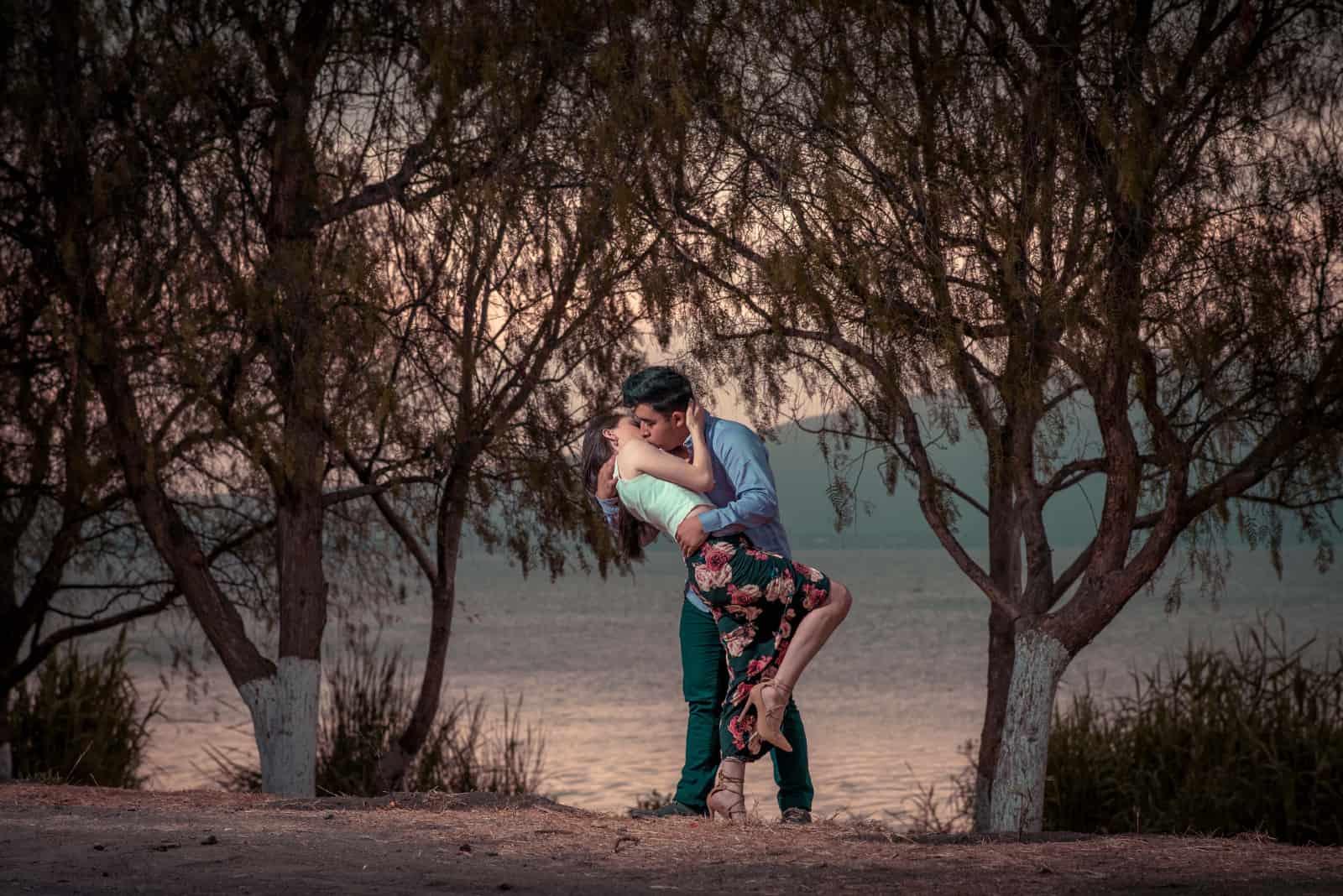 homme et femme s'embrassant près d'un arbre