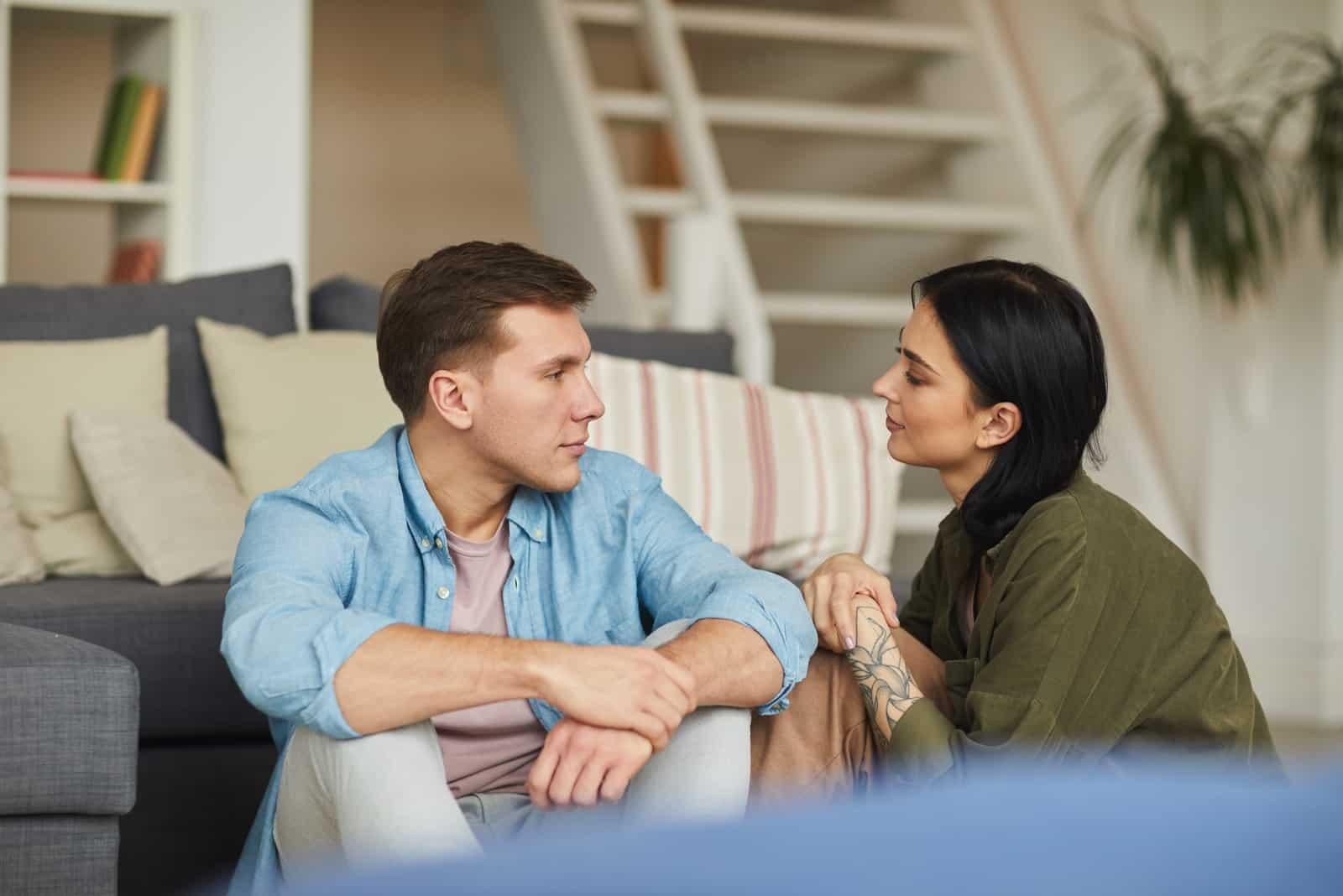 Un homme et une femme se regardent dans les yeux assis sur le sol