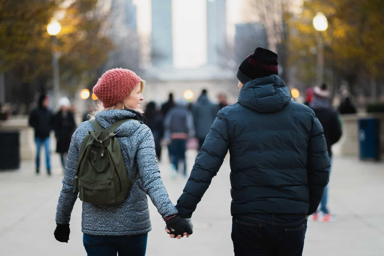 homme et femme se tenant la main en marchant dans la rue