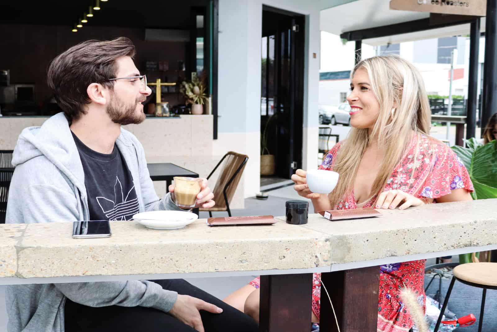 homme et femme prenant un café assis en plein air