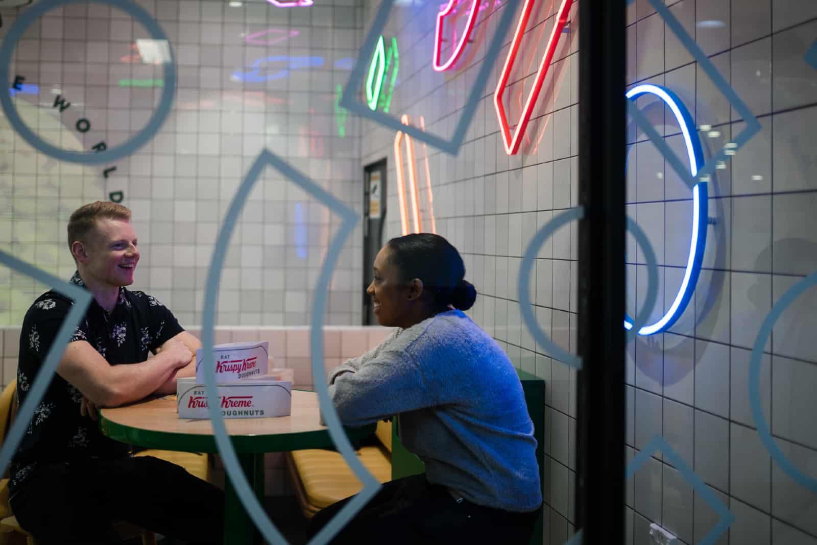 homme et femme discutant assis à une table