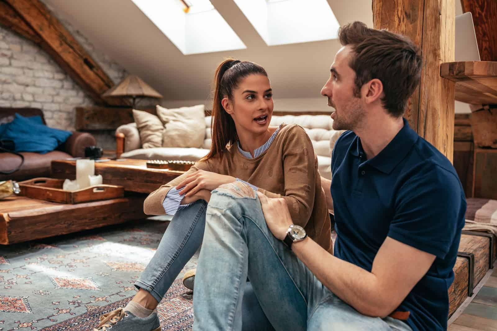 homme et femme parlant assis sur le sol