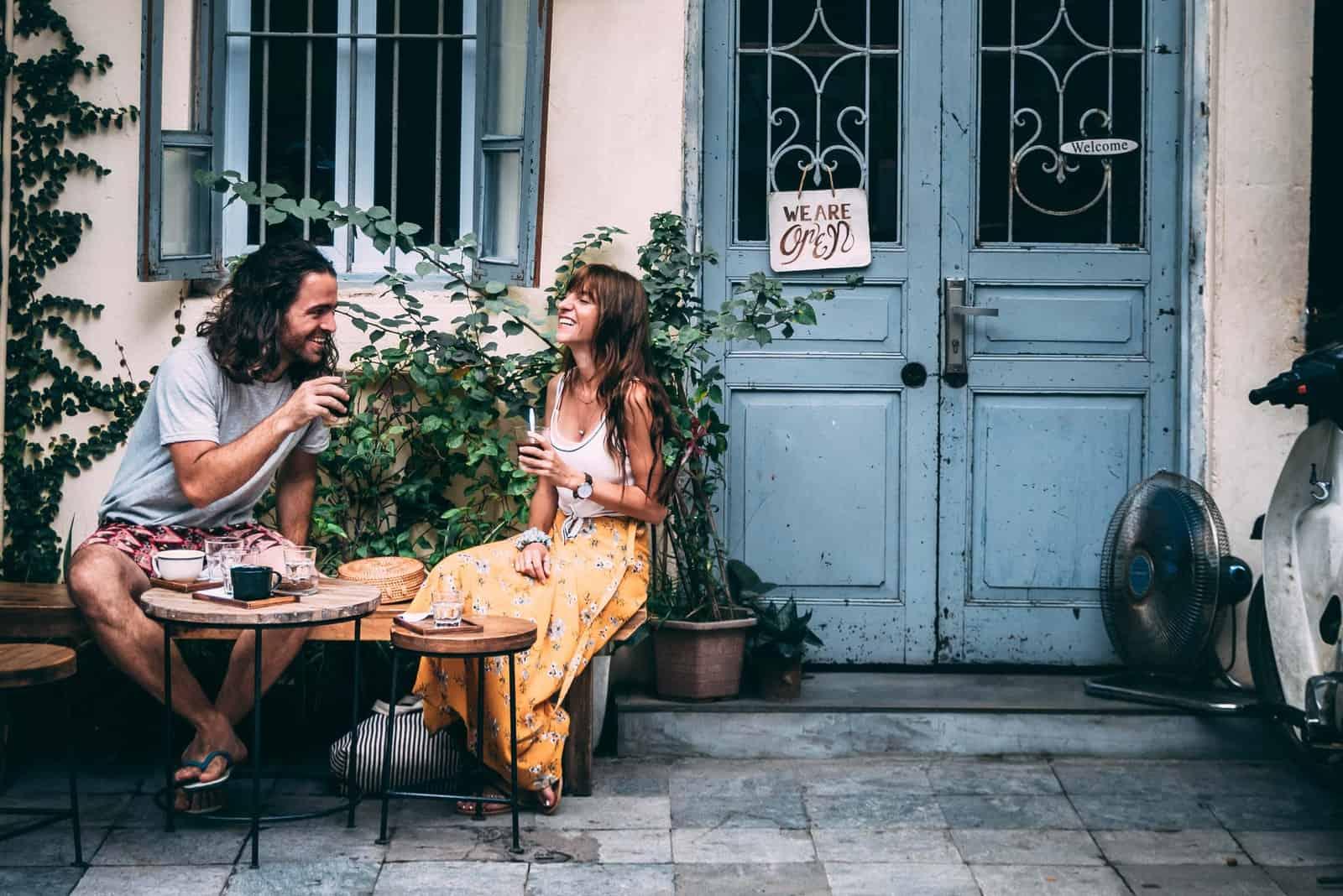 homme et femme riant assis près d'une porte bleue