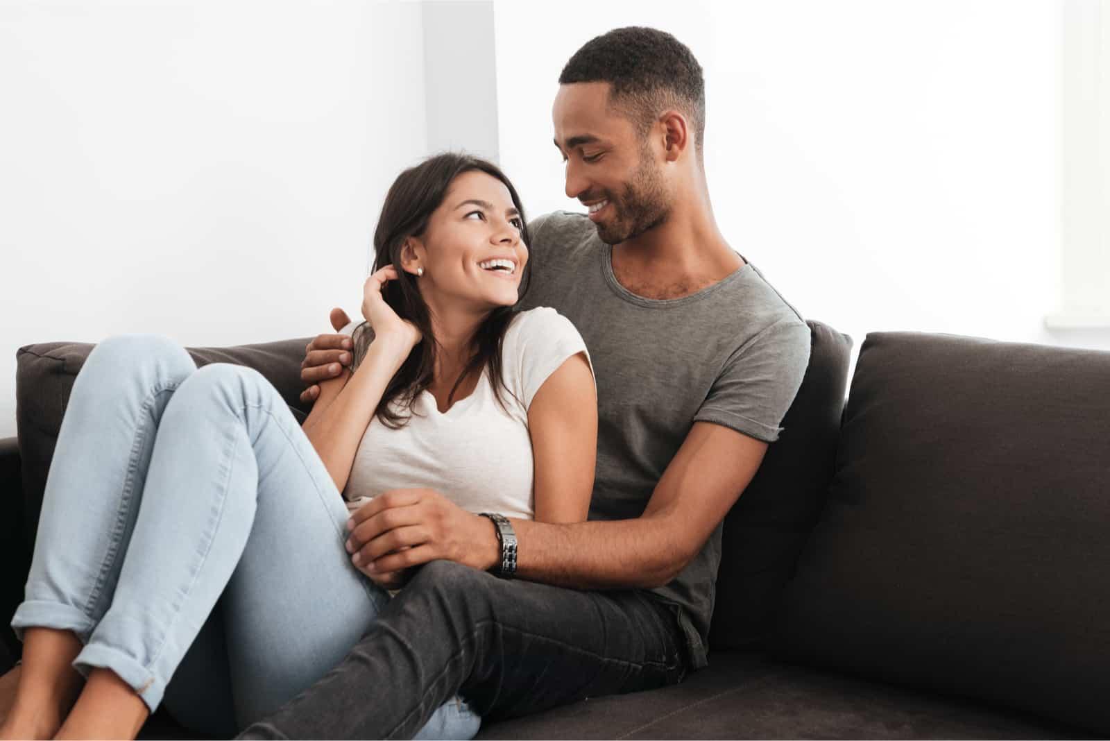 homme et femme riant assis sur un canapé